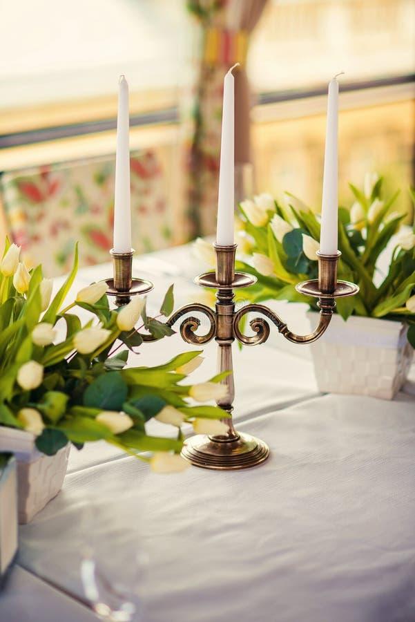 Винтажный бронзовый подсвечник с свечами на таблице с букетами белых тюльпанов стоковая фотография