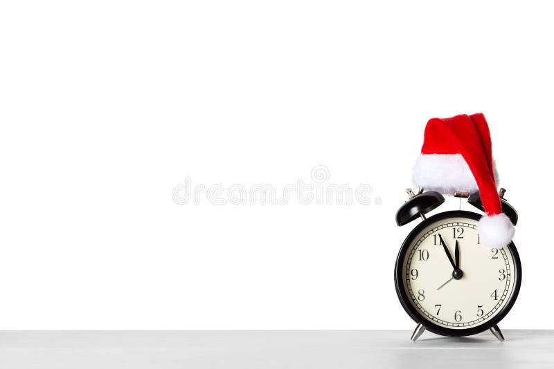 Винтажный будильник со шляпой Санта Клауса и светами феи на предпосылке стоковые изображения