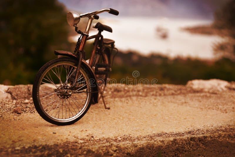 Винтажный велосипед припаркованный на дороге стоковое изображение