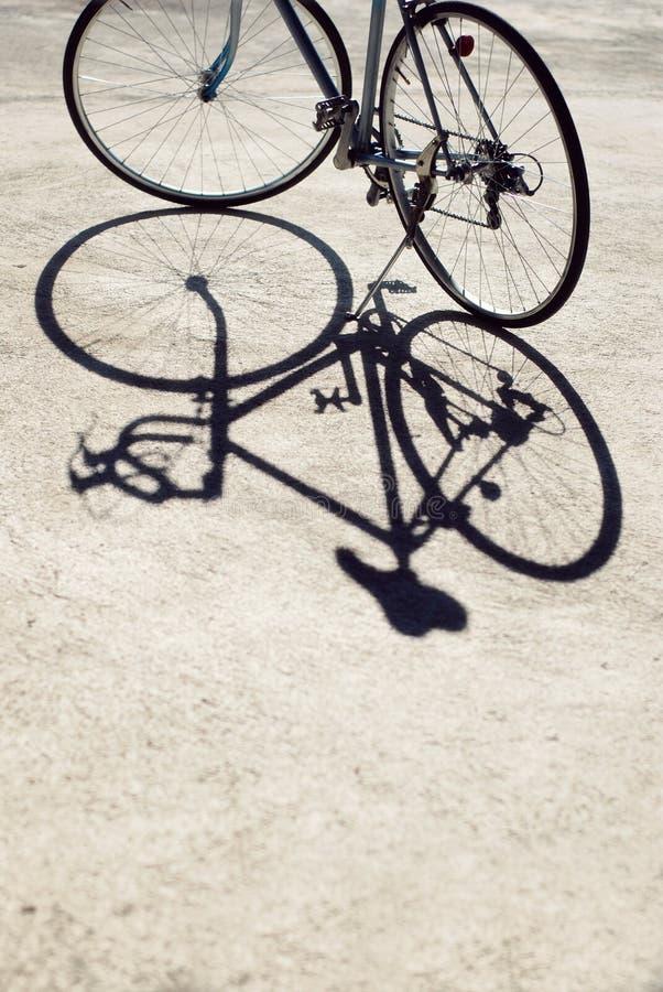 Винтажный велосипед дороги и своя тень стоковые изображения