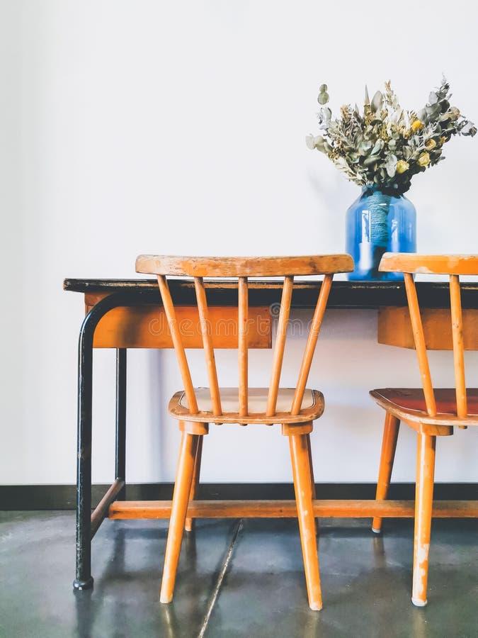 Винтажный деревянный стол начальной школы и 2 деревянных стуль с высушенной цветочной композицией в голубой вазе против белой сте стоковое фото