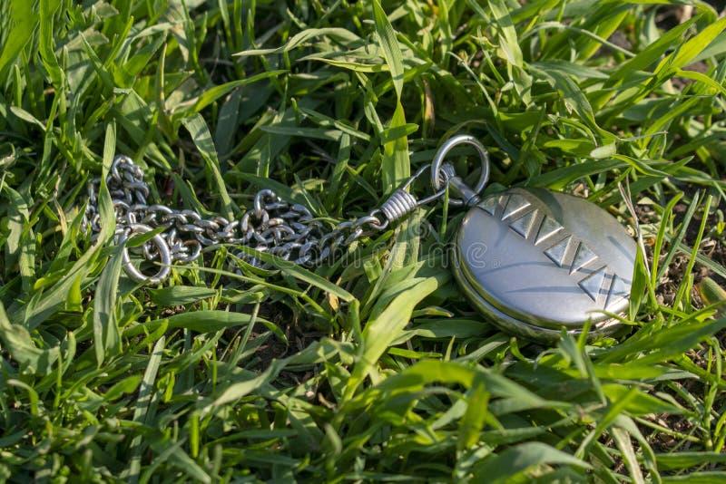Винтажный дозор кармана в закрытой лож формы на зеленой траве Механизм часов не видим o стоковая фотография