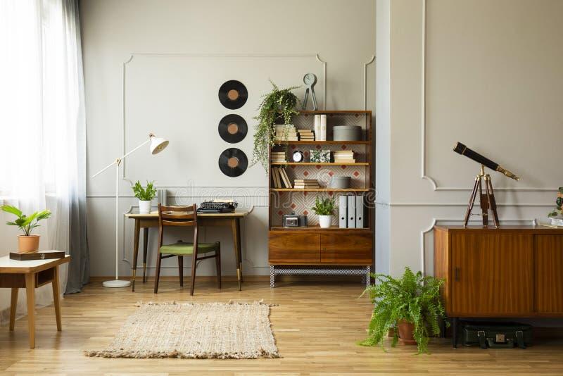 Винтажный домашний офис стиля со столом с машинкой и книжными полками рядом с ним, реальным фото стоковые фотографии rf