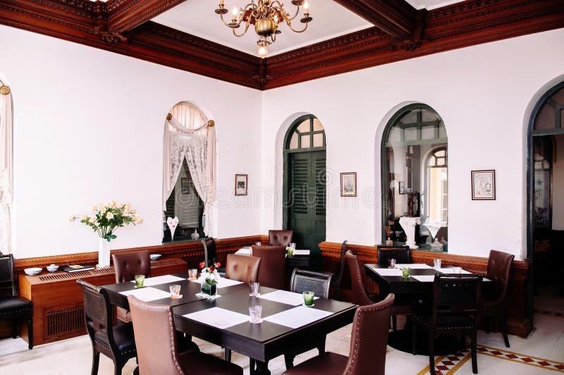 Винтажный дом стиля внутренний с ретро обеденными столами и стульями, колониальным строя интерьером стоковое фото rf