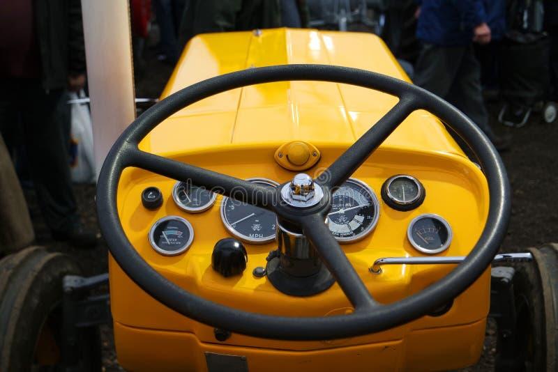 Винтажный желтый трактор и рулевое колесо стоковые изображения rf