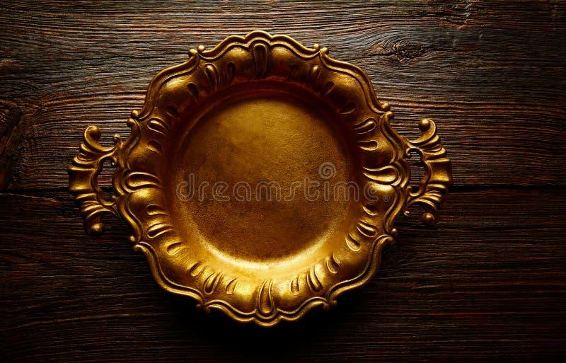 Винтажный золотой поднос круглый на постаретой коричневой древесине стоковое изображение rf