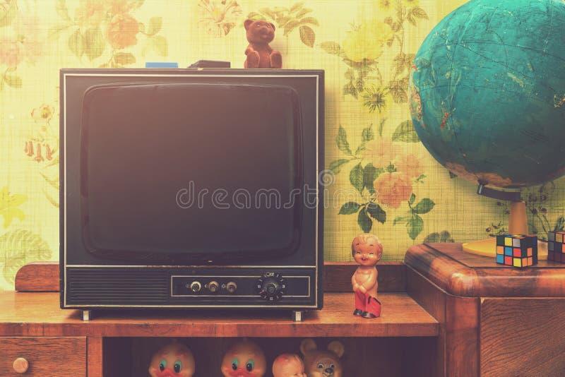 Винтажный интерьер комнаты с ретро ТВ и глобус на стойке телевидения стоковые фотографии rf