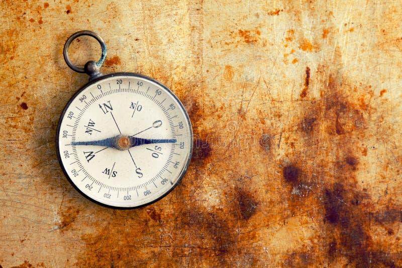 Винтажный компас на винтажной коричневой желтой металлической текстуре Аппаратура географического исследования проводя для искать стоковая фотография rf