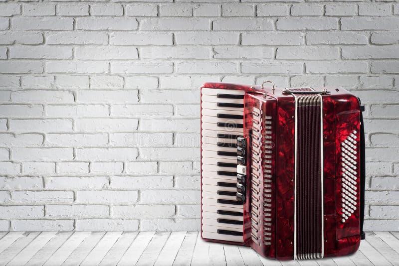 Винтажный красный аккордеон на предпосылке кирпичной стены стоковое изображение rf