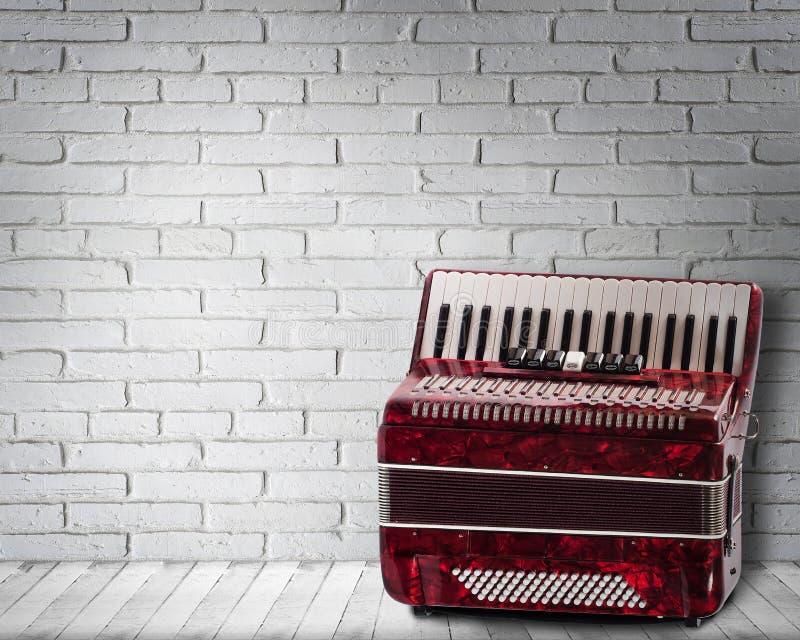 Винтажный красный аккордеон на предпосылке кирпичной стены стоковые фотографии rf