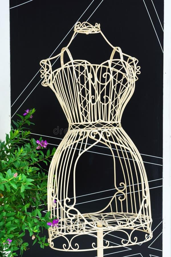 Винтажный манекен портноя открыт-работы провода металла на стойке на черной предпосылке с графической картиной В горшке цветок Ши стоковое фото rf