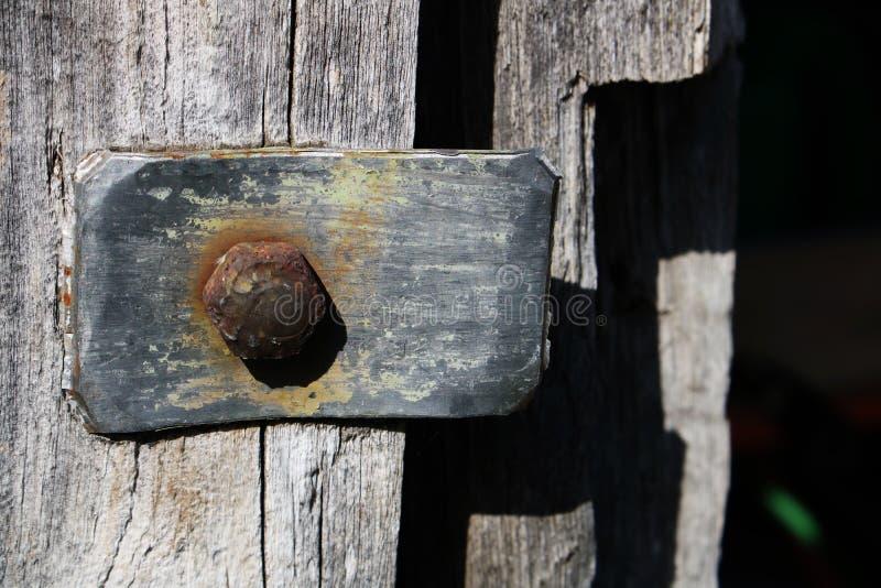 Винтажный металлический элемент с ржавым болтом на предпосылке серой деревянной двери в старом получившемся отказ амбаре стоковая фотография rf