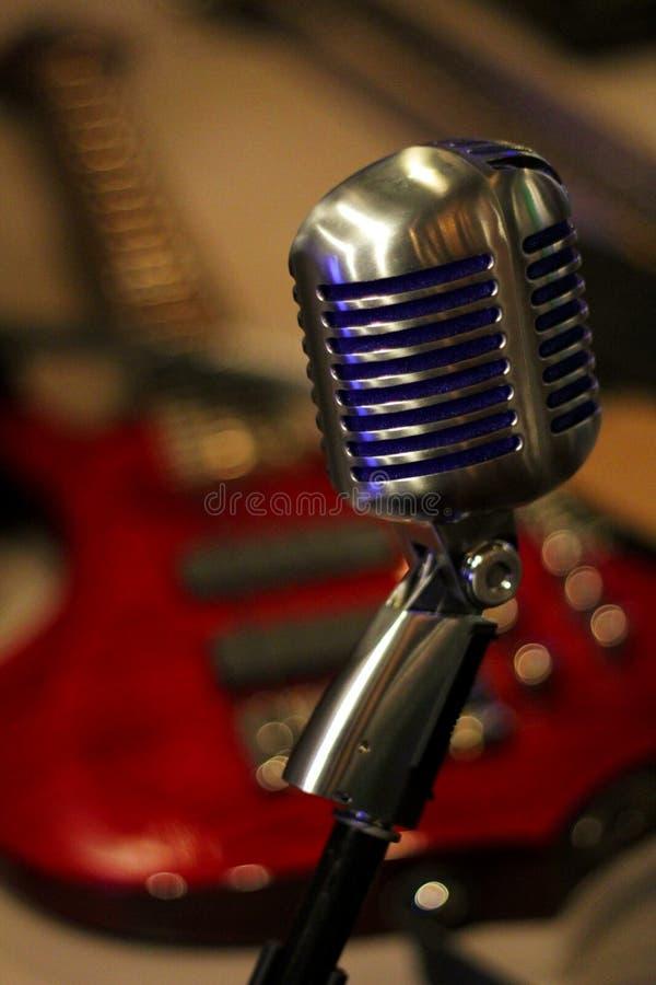 Винтажный микрофон с красной электрической гитарой в предпосылке стоковая фотография