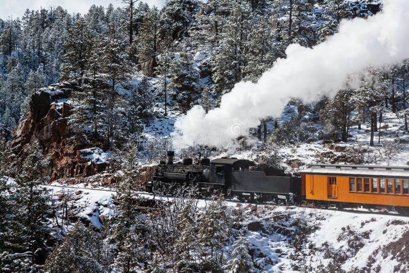 Винтажный паровой поезд, курящий по горам стоковое изображение rf