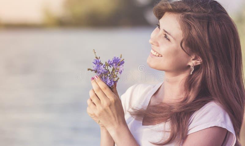 Винтажный портрет счастливой молодой женщины с букетом голубых полевых цветков в их руках на зоре стоковые изображения rf