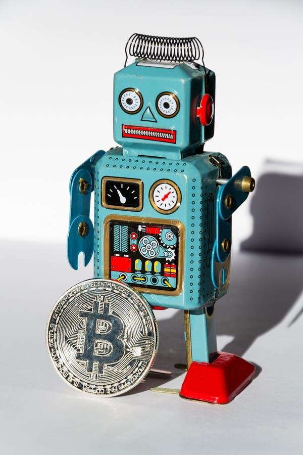 Винтажный робот игрушки олова с монеткой bitcoin, концепцией минирования cryptocurrency стоковое фото rf