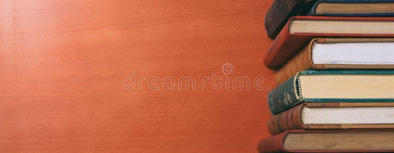 Винтажный стог книг на деревянной предпосылке - скопируйте космос стоковое изображение