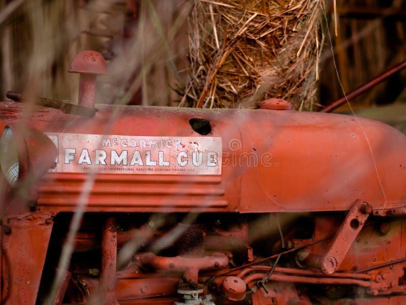 Винтажный трактор сидя в амбаре стоковое фото