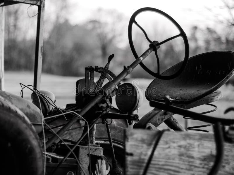Винтажный трактор сидя в амбаре стоковые фото