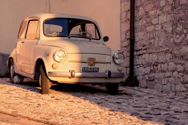 Винтажный Фиат 500 припарковал в улице средневекового городка Италия, 2011 стоковые изображения rf