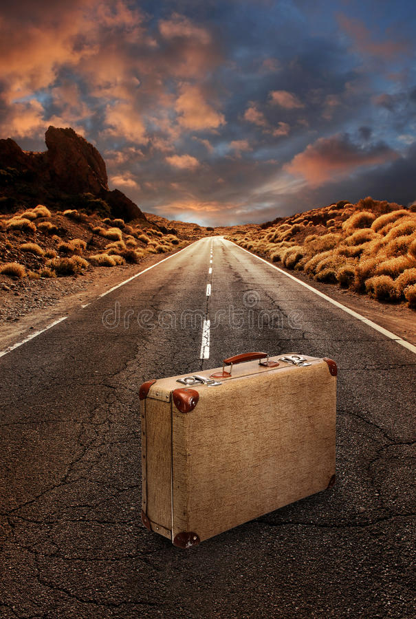 Винтажный чемодан на дороге через пустыню стоковое фото rf