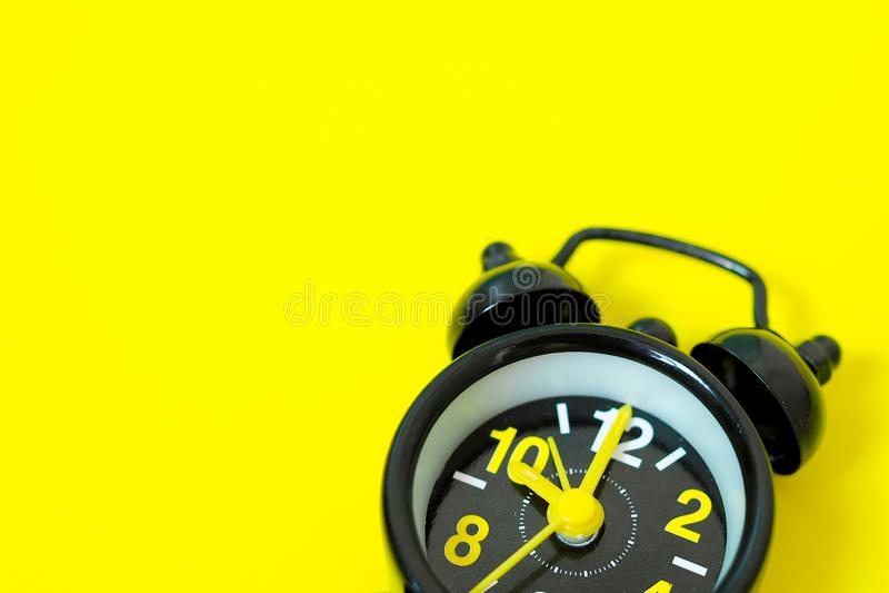 Винтажный черный будильник изолированный на желтой предпосылке с космосом для дизайна стоковая фотография rf