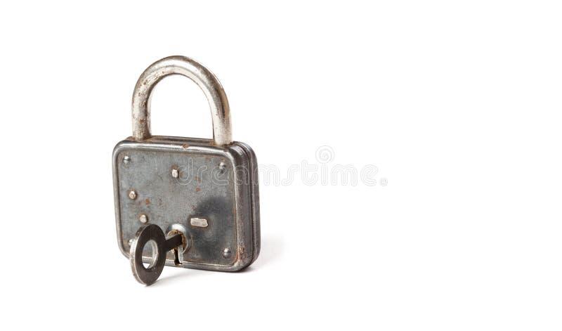 Винтажный padlock с ключом в отверстии конец-вверх замка смертной казни через повешение текстура и детализированный Белая предпос стоковые фотографии rf