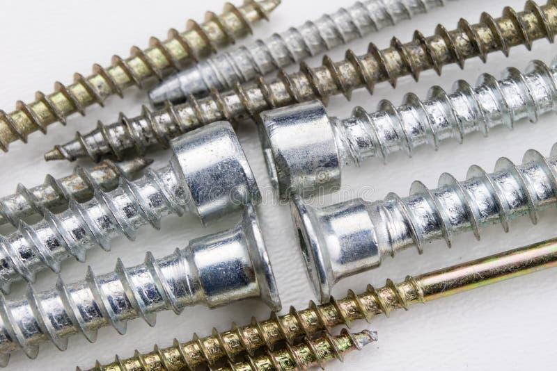 Винты на белой таблице Аксессуары для соединений винта стоковые изображения rf