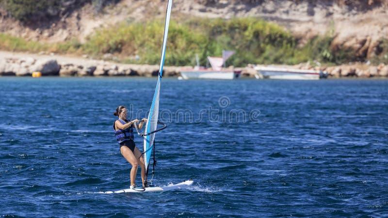 Виндсерфинг женщины в открытых морях стоковое фото