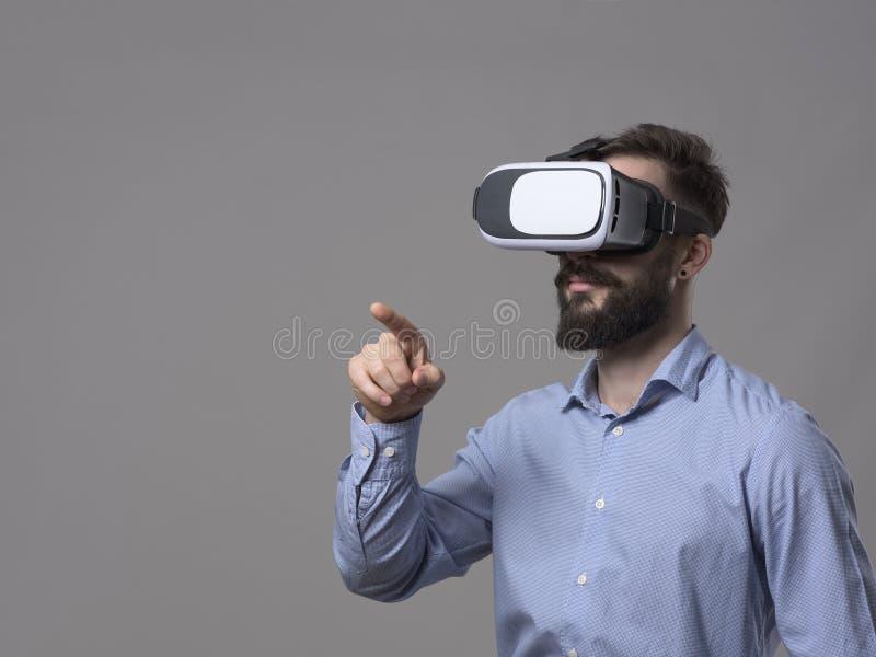 Виртуальная реальность бизнесмена нося стекла указывает палец и взаимодействует с увеличенным экраном касания реальности с copysp стоковая фотография rf