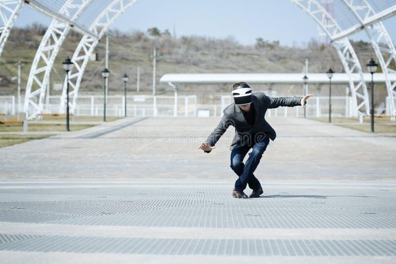 Виртуальная реальность человека нося стекла в городе играет игры как реальное время стоковое изображение