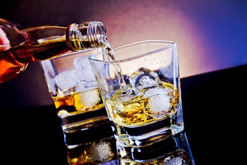 Виски бармена лить перед стеклом вискиа на светлом диско сини подкраской стоковые изображения