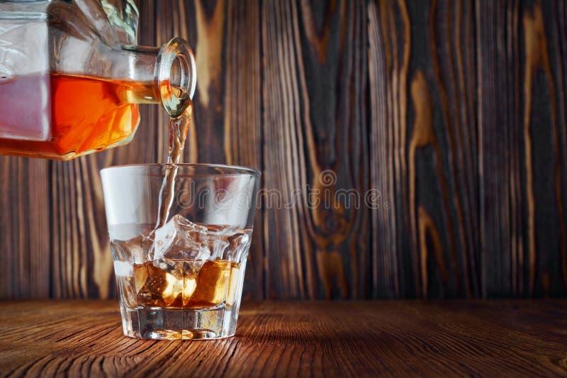 Виски сильного алкогольного напитка шотландский льет от графинчика в старом стекле моды с кубом льда стоковые фотографии rf