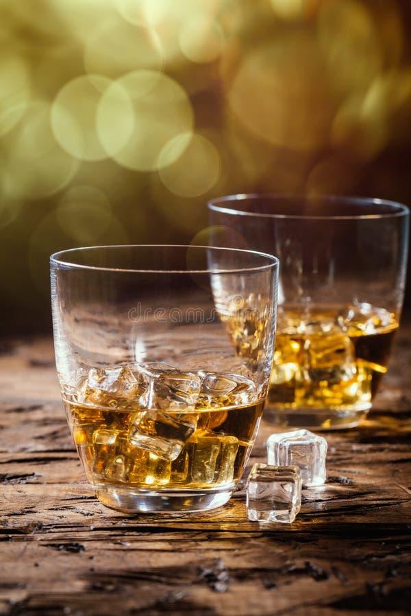 Виски с льдом в стеклах на деревенской деревянной предпосылке стоковое фото