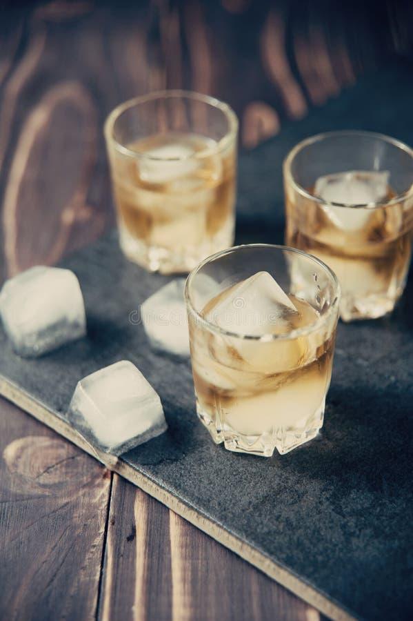 Виски с льдом в стеклах, деревенской деревянной предпосылкой стоковые фотографии rf