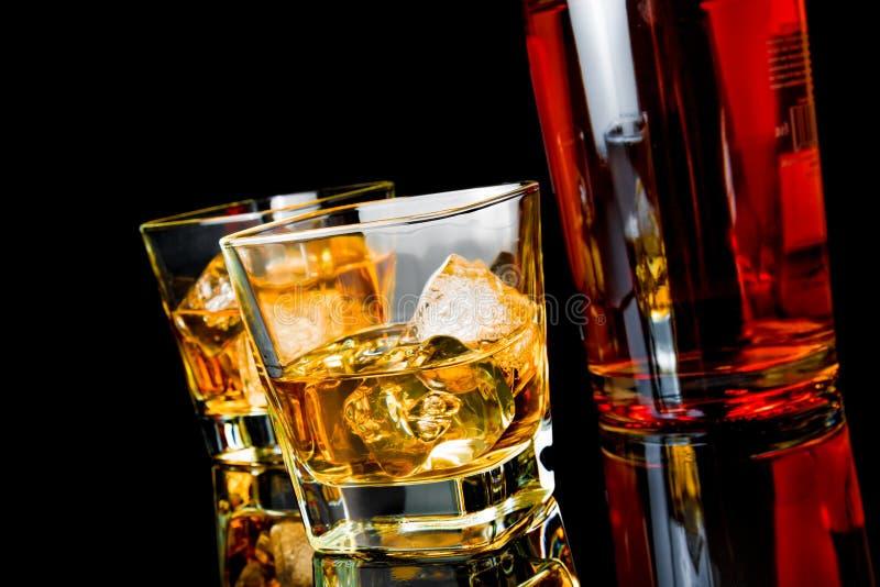 Виски 2 с льдом в стеклах приближает к бутылке на черной предпосылке стоковые изображения rf