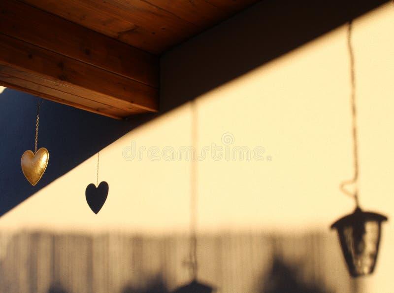 Вися золотое сердце с тенями в предпосылке стоковые изображения rf