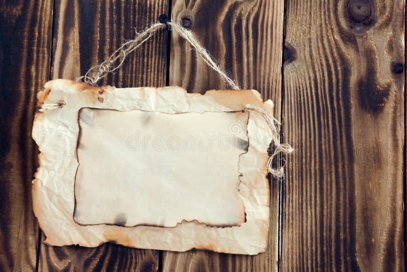 Вися, который палят бумага на деревянной предпосылке стоковые фотографии rf