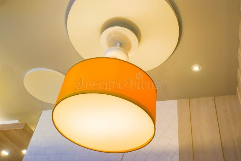 Вися лампа дизайна оранжевого зарева творческая на потолке ресторана для украшения стоковое изображение rf