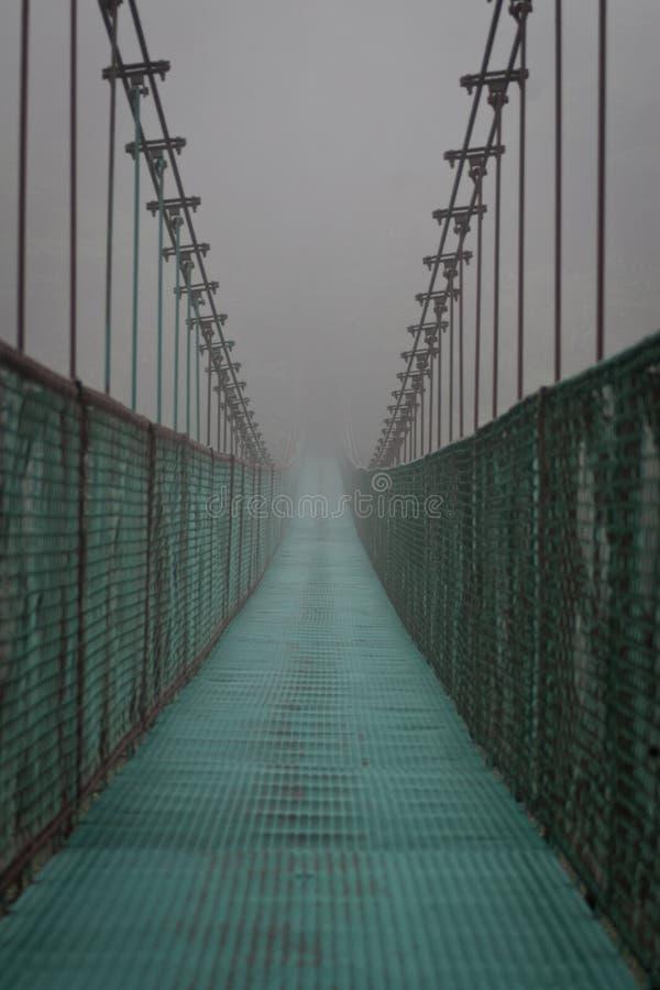 Вися мост в тумане стоковая фотография