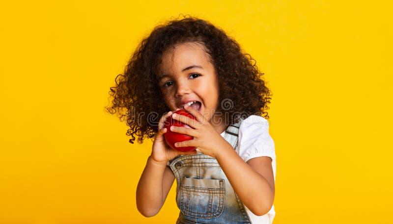 Витамин Маленькая девочка кусает красное яблоко стоковое фото