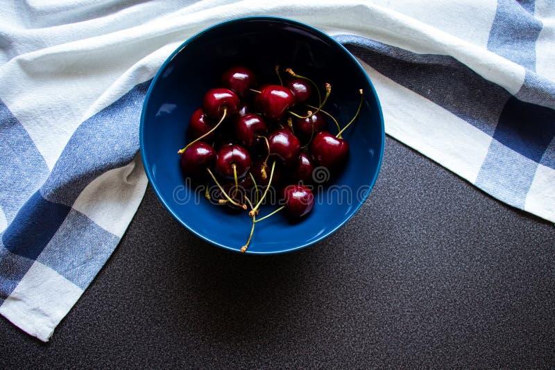 Вишни в керамическом шаре на темном полотенце предпосылки и кухни с линией r стоковая фотография