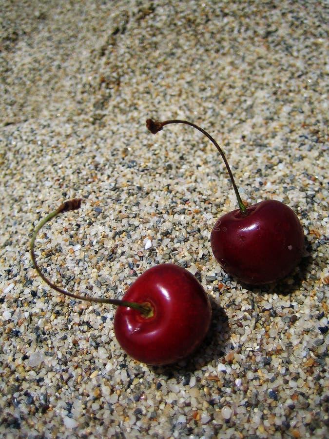 2 вишни на предпосылке макроса пляжа стоковое изображение rf