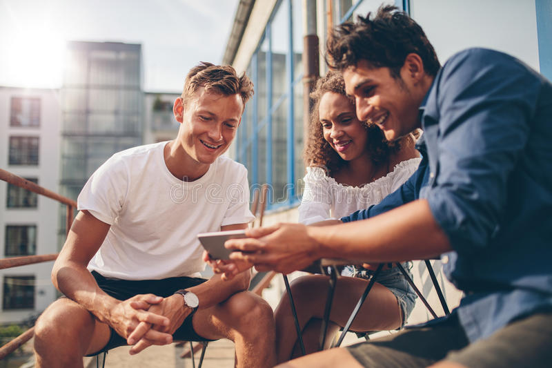Видео группы людей наблюдая на мобильном телефоне стоковое фото