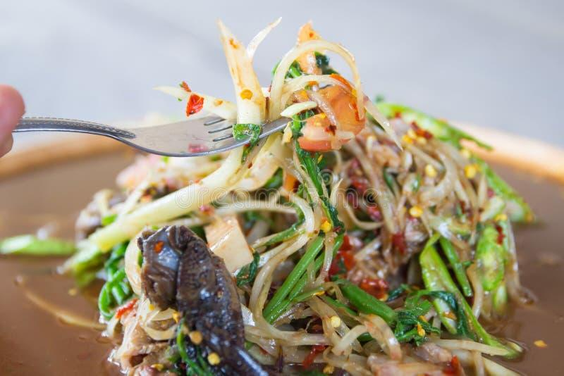Вилка владением руки принимает папапайе пряный салат с испеченными свининой и крабом стоковое фото rf