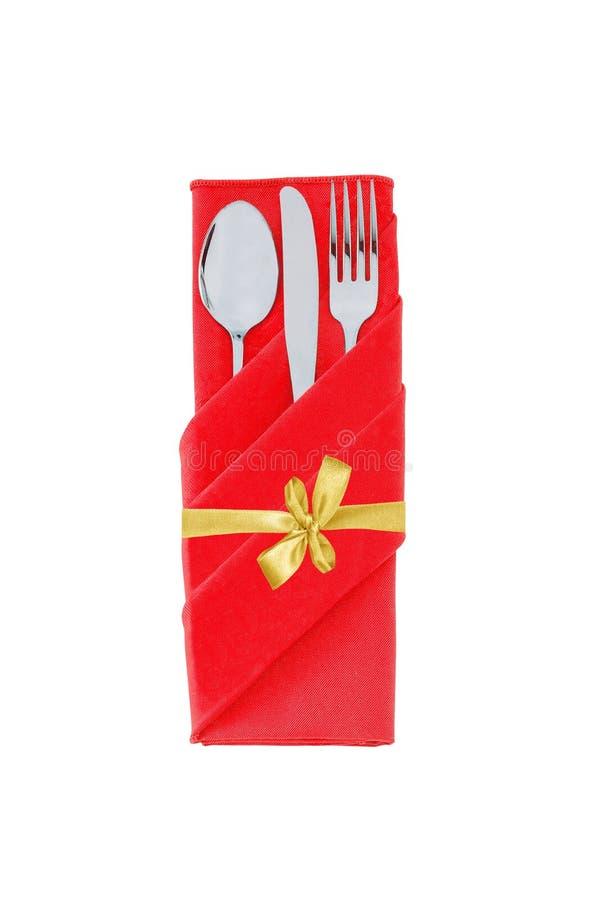 Вилка, ложка и нож в красной ткани при золотой смычок изолированный на w стоковая фотография
