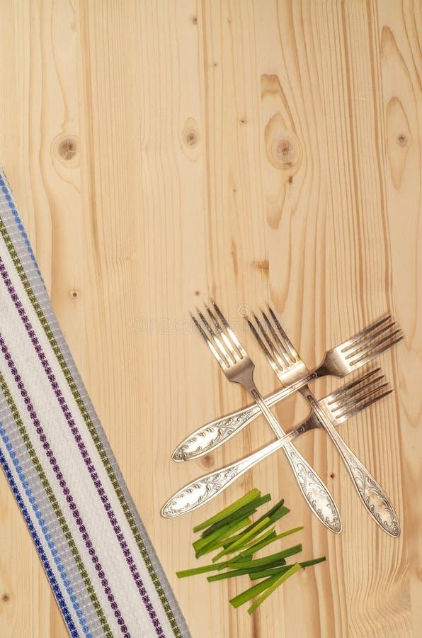 4 вилки, лук-порей и полотенца на деревянном столе стоковое изображение