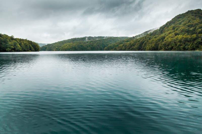 Вид на озеро с темной водой бирюзы с малыми волнами и moun стоковое изображение rf