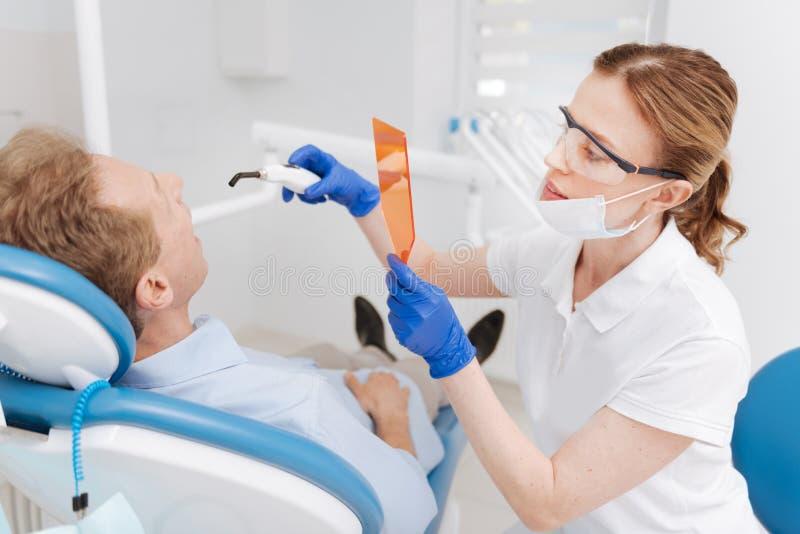 Видно скрупулезный дантист забеливая зубы пациентов стоковое изображение rf