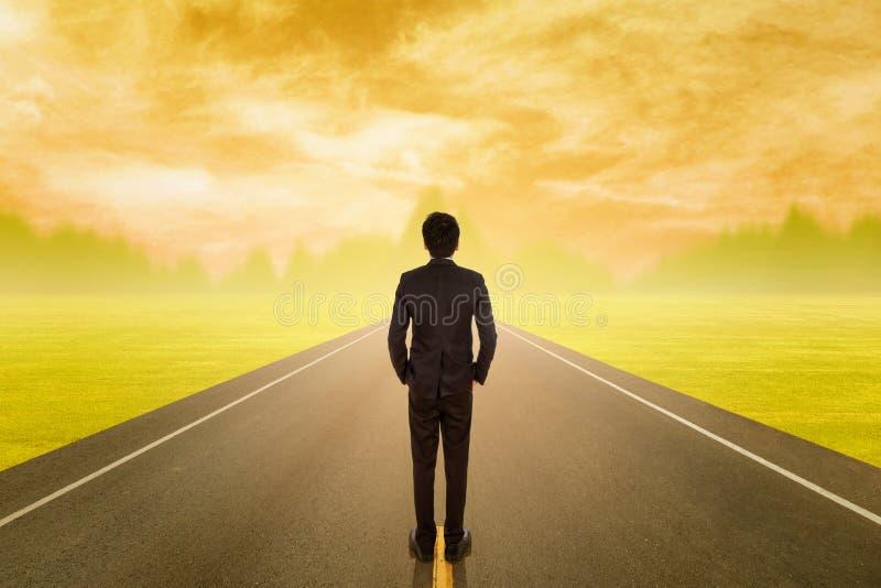 Вид сзади бизнесмена при чемодан стоя на дороге стоковое изображение